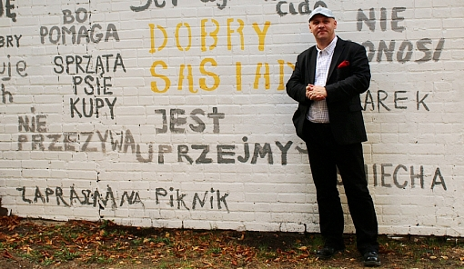 Piotr Waglowski na tle ściany z wpisami o dobrym sąsiedzie