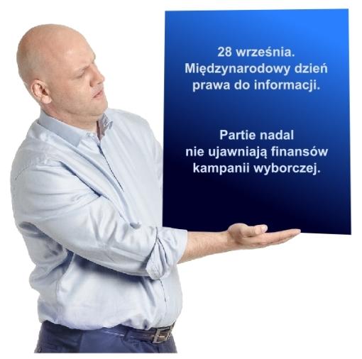 Piotr Waglowski z tablicą informującą o międzynarodowym dniu prawa do informacji